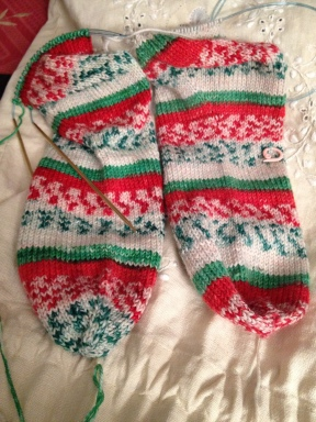 i have two pairs of socks on the needles one cuff down in a speckled yarn and a toe up pair in heritage print by cascade in christmas colors